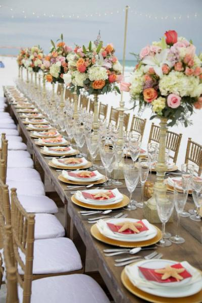 Chic Reception In Destin Florida Farm Tables With Gold Chiavari Chairs Chargers White Plates Flatware And Rimmed Glassware